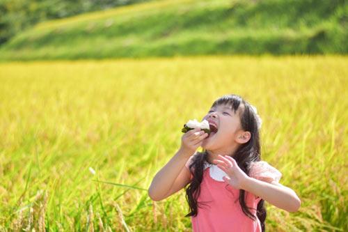 笑顔でおにぎりを食べる子ども